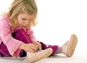 Девочка надевает ботинки