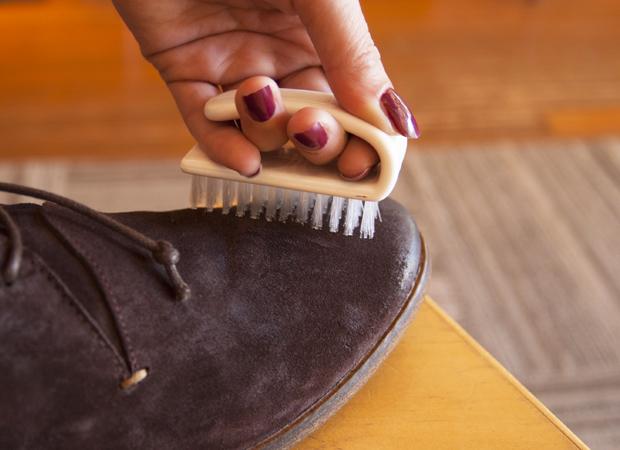 Девушка чистит обувь из нубука