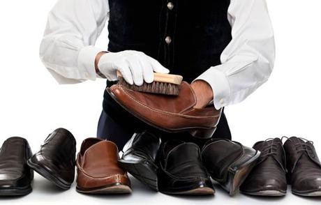 Мужчина наносит крем на кожаную обувь