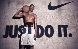 Мужчина с мячом у плаката Nike