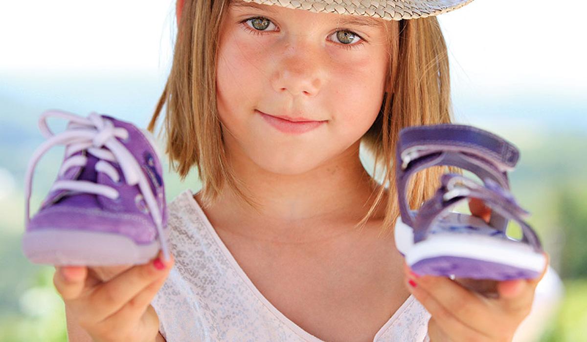 девочка держит кроссовки